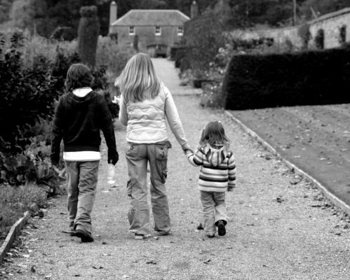 Three children holding hands and walking